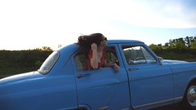 Happy girl in sunglasses leaning out of retro car window and enjoying trip. Young woman looking out window of moving old. Auto on sunny day. Travel and freedom stock footage