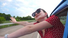 Happy girl in sunglasses leaning out of vintage car window and enjoying trip. Young woman looking out window of moving. Old retro auto and raising hand. Travel stock footage