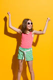 Happy girl in the sunlight. Happy teen girl with arms raised. Three quarter length studio shot on yellow background Royalty Free Stock Photo