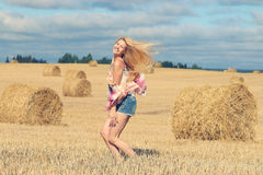 Happy girl in sunny autumn field Stock Photography