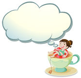 A happy girl swimming above the cup with an empty cloud template Royalty Free Stock Photography