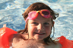 Happy girl swimming in pool stock images