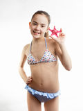 Happy girl in swimming suit showing red starfish Stock Photography