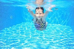 Happy girl swims in pool underwater, active kid swimming and having fun Royalty Free Stock Images