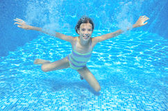 Happy girl swims in pool underwater, active kid swimming and having fun Royalty Free Stock Photos