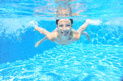 Happy girl swims in pool underwater, active kid swimming and having fun Stock Photos