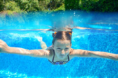 Happy girl swims in pool underwater, active kid swimming and having fun Royalty Free Stock Photography