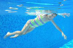 Happy girl swims underwater in pool Royalty Free Stock Photo