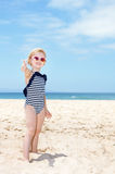 Happy girl in swimsuit on a white beach showing thumbs up Royalty Free Stock Photos