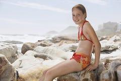 Happy Girl In Swimwear Sitting On Rock Stock Images