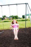 Happy girl on swing. Happy young girl on swing with thumb up, grass and houses in background Stock Image