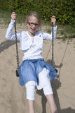 Happy girl on swing. Happy blonde girl with glasses playing on a swing Royalty Free Stock Image