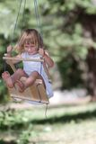 Happy girl on swing in park Royalty Free Stock Photos