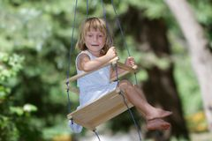 Happy girl on swing in park Stock Photo