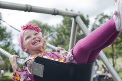 Happy girl swinging in the park Stock Image