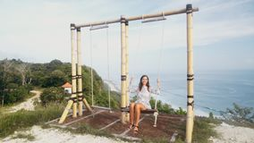 Happy girl swinging on swing over cliff with beautiful view on ocean, slow motion. Girl relaxes on holidays stock footage