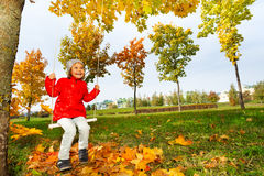 Happy girl on swings smiles cheerfully and looking. Happy girl sitting on swings, smiling cheerfully, looking up during autumn sunny day in park Royalty Free Stock Photos