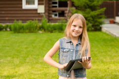 Happy girl with tablet computer looking at camera Royalty Free Stock Photos