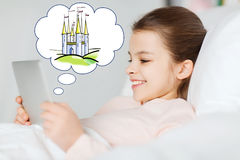 Happy girl with tablet pc dreaming of fairy castle Royalty Free Stock Images