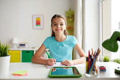 Happy girl with tablet pc and notebook at home Stock Photo