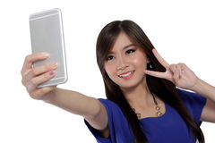 Happy girl take a self-shot photo using her phone. Cute Asian girl smile and make victory sign while take a self shot photo with her smartphone front camera Royalty Free Stock Photo