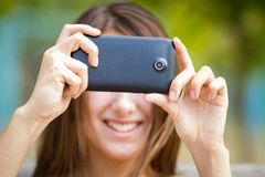 Happy girl taking photo with camera phone Royalty Free Stock Photography