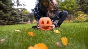 Happy girl taking pumpkin Jack in hands, playing in yard, Halloween celebration. Stock photo royalty free stock image