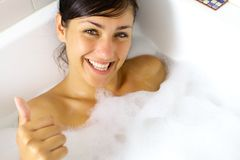 Happy girl taking relaxing bath thumb up Stock Images