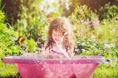 Happy girl taking water procedures in summer garden. Royalty Free Stock Photography