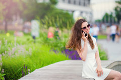 Happy girl talk by smartphone outdoors in the park. Young attractive woman with mobile phone outdoors enjoying holidays Stock Photos