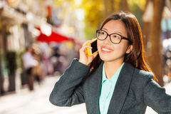 Happy girl talking on the mobile phone at street Stock Photos