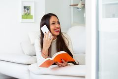 Happy girl talking on the phone with her friends and holding a book in her hand stock photo