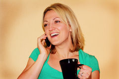 Happy girl talking on phone holding mug Royalty Free Stock Image