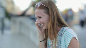 Happy girl talking by smart phone in a city stock footage