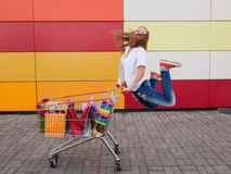 Girl  with shopping trolley. The happy girl the teenager joyfully jumps near to the cart full of purchases stock photography