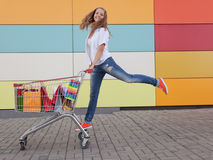 Girl with shopping trolley. The happy girl the teenager joyfully jumps near to the cart full of purchases stock image