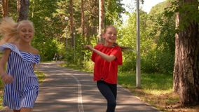 Happy girl teenager running on path in summer park. Smiling girl friends running on sidewalk and jumping front camera in stock video footage