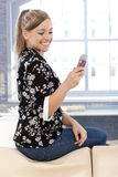 Happy girl texting on mobile at home Royalty Free Stock Photos