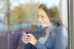 Girl texting using a smart phone at home. Happy girl texting using a smart phone sitting on a couch at home Royalty Free Stock Photography
