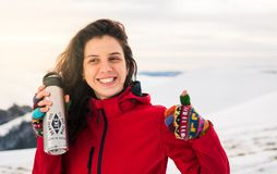 Happy girl with thermos on snowy mountain stock image