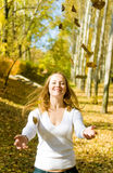 Happy girl throwing leaves Stock Photography