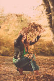 Happy girl is throwing leaves up to the air. Stock Photography