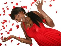 Happy Girl Throwing Rose Petal. Happy african american girl wearing hot red fashion dress throwing rose petal Stock Photography