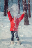 Happy girl throwing snow in the air on sunny day stock photo