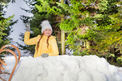 Happy girl throwing snowball from the snow tower Royalty Free Stock Images