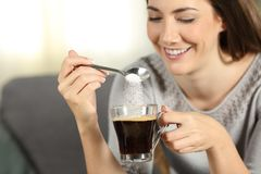 Happy girl throwing sugar into coffee with a spoon. Close up of a happy girl throwing sugar into coffee with a spoon sitting on a couch in the living room at Royalty Free Stock Photos