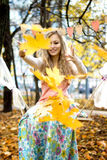 Happy girl throws colorful autumn leaves Stock Images