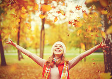 Happy girl throws up autumn leaves in park for walk outdoors Royalty Free Stock Image