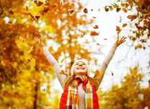 Happy girl throws up autumn leaves in park for walk outdoors. Happy girl throws up autumn leaves in the park for a walk outdoors Stock Photography