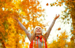 Happy girl throws up autumn leaves in park for walk outdoors Stock Photography
